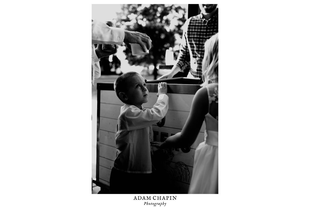 black and white photos of little kid trying to stand on tip toes to see ice cream options during wedding reception