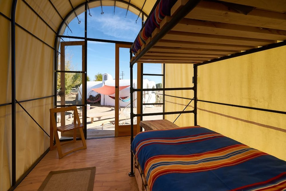 QUONSET HUT SPECS  (2) twin bunk beds / sleeps 1-3 Room for additional cot   Power / electric heat / lighting   Under bed crate storage   Working desk for 1 with a view   Outdoor lounge chairs   Small Porch deck
