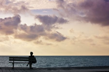 123rf.com (c) David Hughes: woman sitting on bench looking out to sea sunset sky