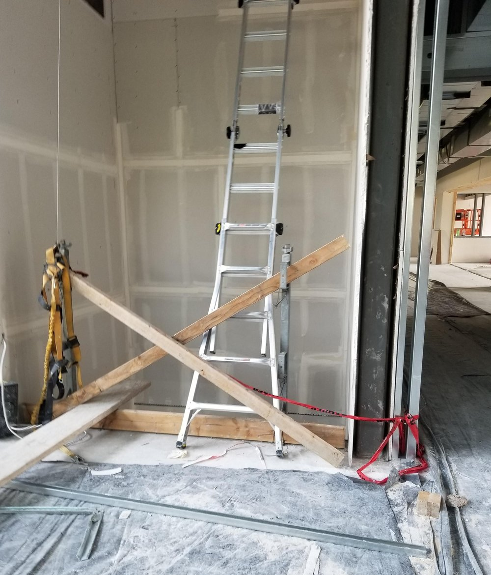 This is one of those WTF photos. What' you're looking at is a ladder for a drywall installer and it spanning the opening of an elevator shaft. The barricade is also ridiculous.