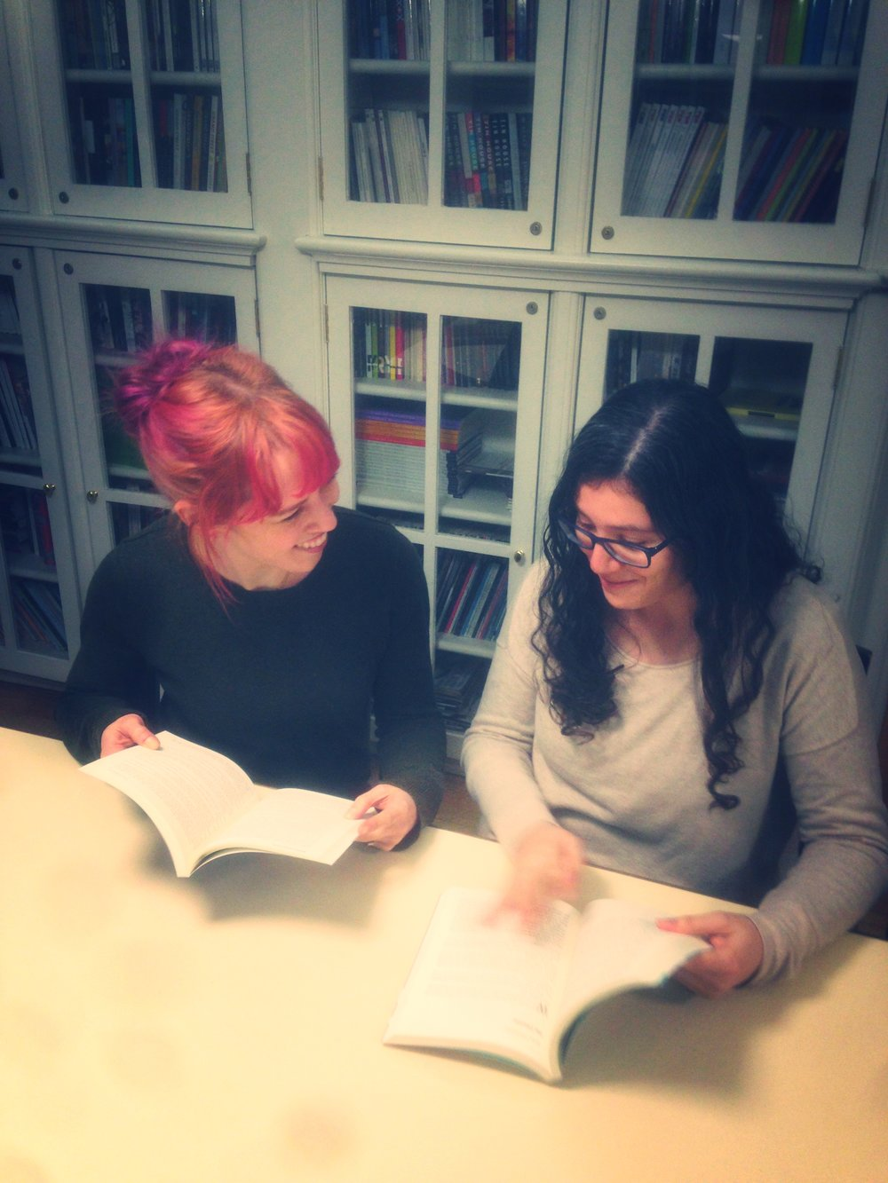 Assistant Fiction Editor Alyssa diPierro (LEFT) and Fiction Editor Bruna Dantas Lobato (RIGHT) pretend to flip through old Washington Square Review journals at the Creative Writing House.