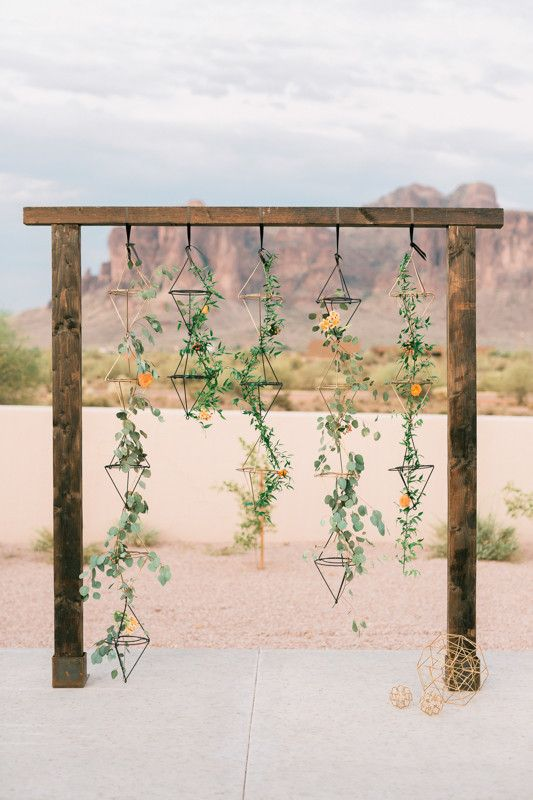 25-geometric-desert-wedding-arbor-with-hanging-greenery-and-color-coordinated-flowers-scattered-throughout.jpg