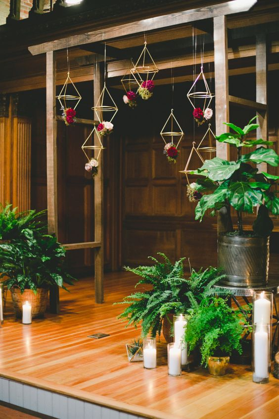 24-an-indoor-wooden-arch-with-hanging-geometric-decor-and-bold-flowers.jpg