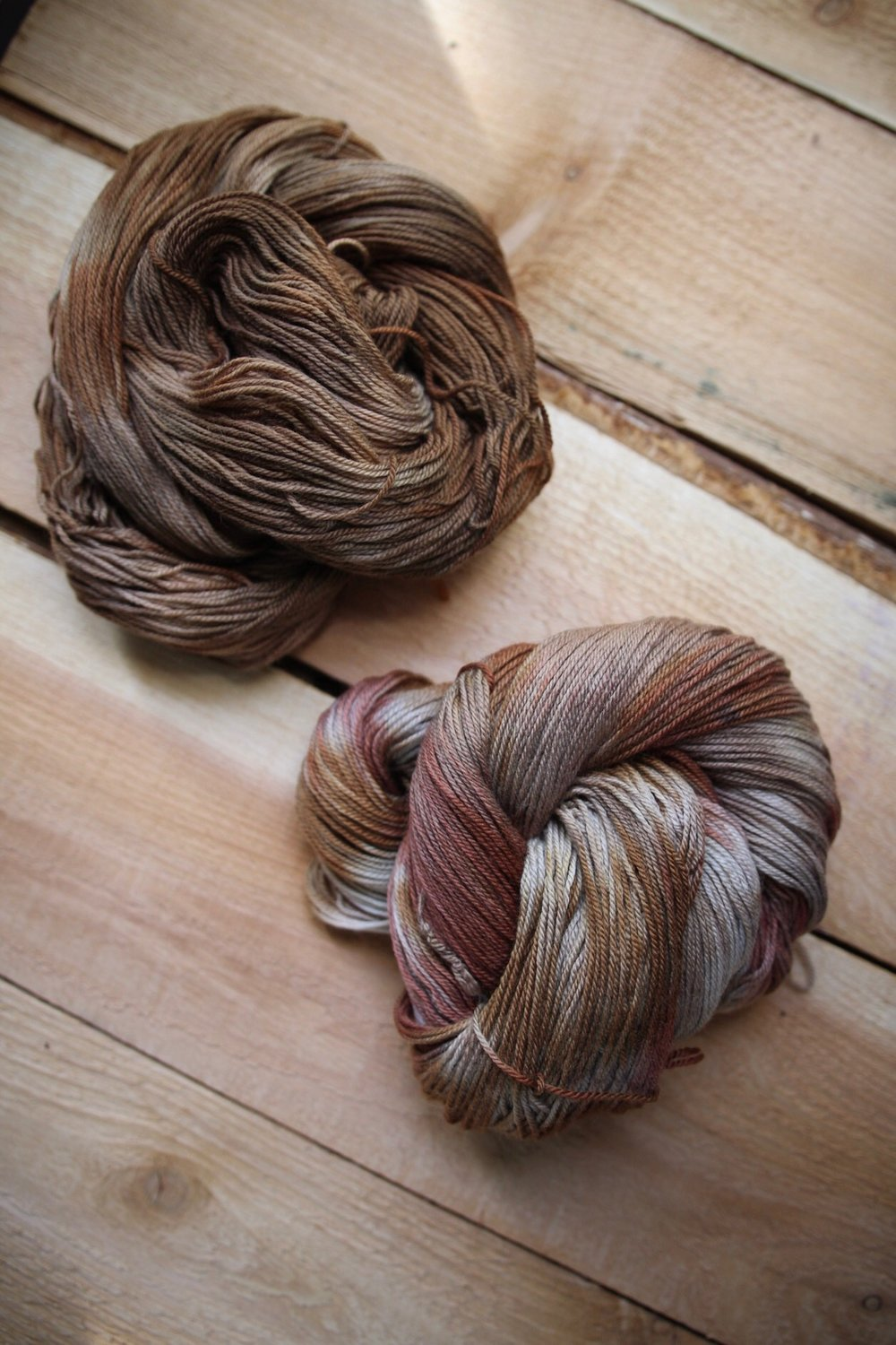 top: iron modified walnut + yellow onion skin (twist-dyed) | bottom: iron modified avocado + yellow onion skin (twist dyed) - both on superwash 80/10/10 base