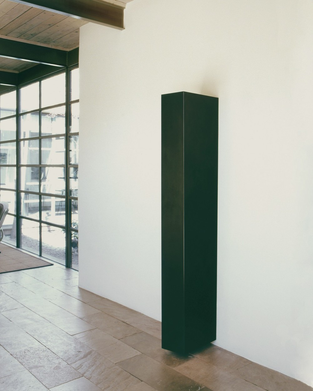 Long rectangle made of graphite, attached to a white wall, but floating just above the floor.