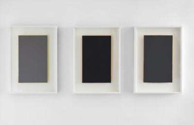 Three of Susan York's  Achromatopsia  series, which are shades of grey with green, orange, and yellow illuminating from behind.
