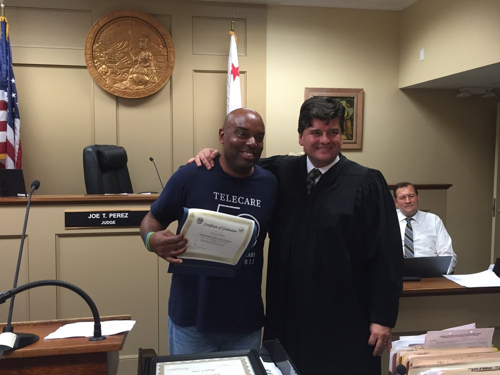 Thurman Williams (left) is handed a graduation certificate for completing the Assisted Intervention program from Judge Joe T. Perez (right).