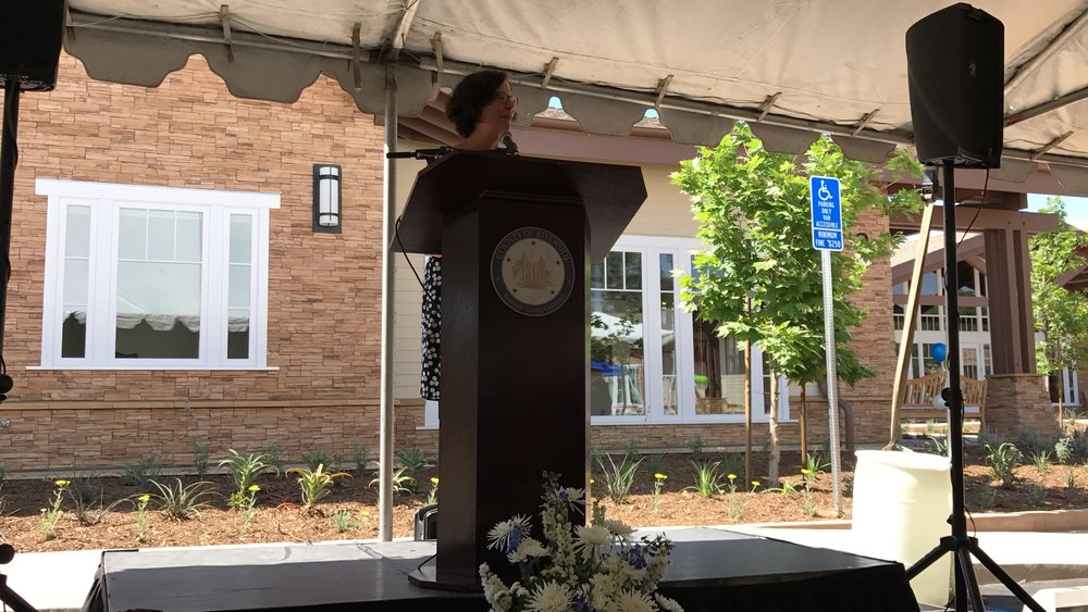Faith Richie, SVP of Development, speaks at the Lagos ribbon cutting ceremony and open house on May 3.