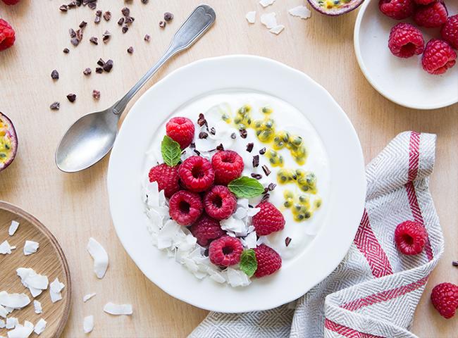 Surpresa de Maracujá   e Frutos Vermelhos   • 1 iogurte Adagio Skyr Natural • 2 maracujás • 50g de framboesas •2 colheres de sopa de lascas de coco •1 colher de sopa de  nibs  de cacau