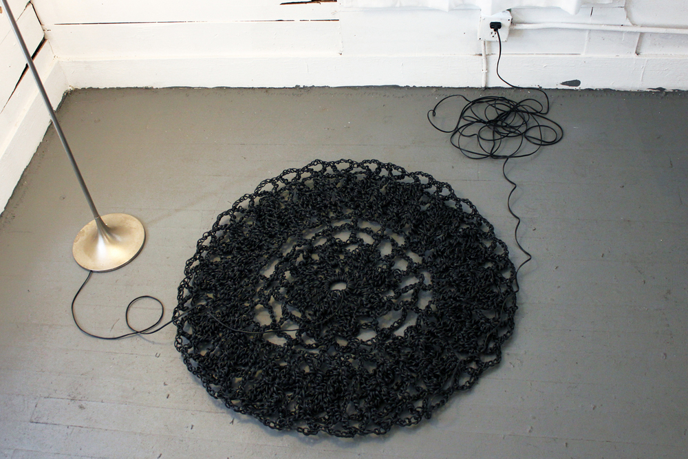 Crocheted from over 1500 feet of electrical wire, the doily powers the light in the room.