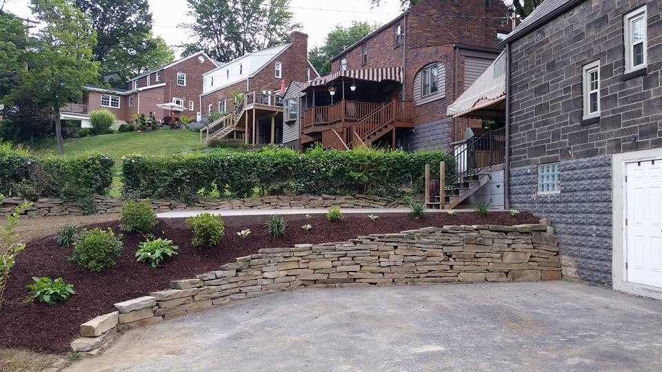 Finished patio with retaining wall and landscape services; mulching and installation of shrubs.