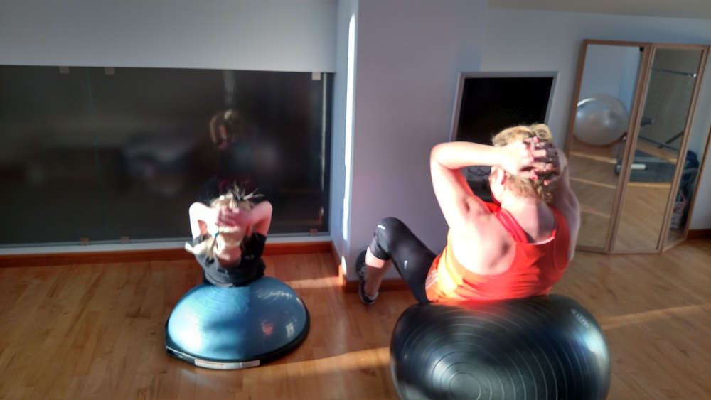 Mother/daughter workout in home gym.