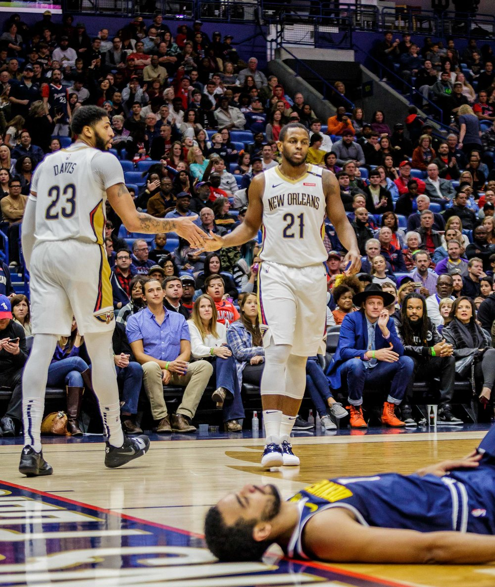 Denver Nuggets forward Trey Lyles (7) lays on the floor after unsuccessfully defending New Orleans Pelicans for­ward Anthony Davis (23) who shakes hands with Darius Miller (21) during the second half of an NBA basketball game in the Smoothie King Center in New Orleans, La. Monday, Nov. 17, 2018. The Pelicans won, 125-115.