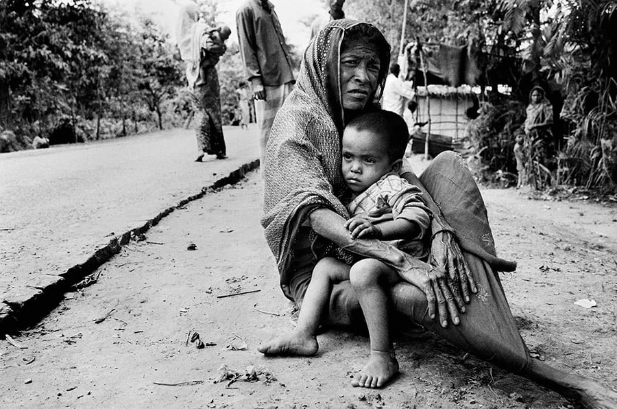 A woman from the stateless Rohingya community sits on the side of the road with her grandchild near Teknaf in southern Bangladesh.