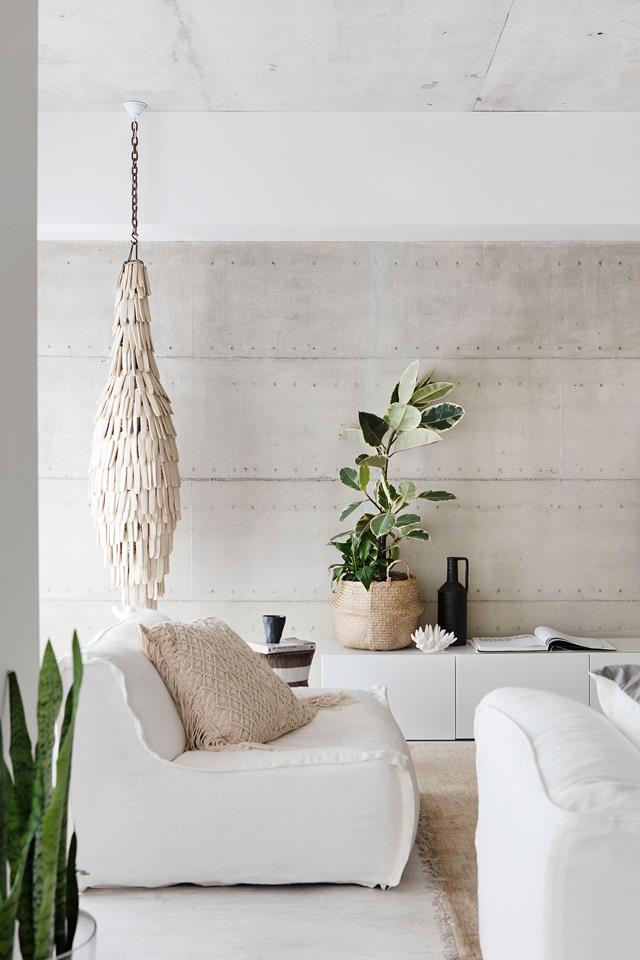 A rammed-earth feature wall, by Lime St Projects, runs the length of the eastern side of the house. Coffee table, sofachair, side table, cushions and white plant pots, all from Blupeter