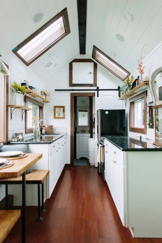 This kitchen actually belongs to a tiny luxury home on wheels. There are lots of clever elements at work here, giving the kitchen a larger feel. The skylights and white base obviously make everything appear spacious, but it's the high end finishes — shelf brackets, hardware, and sliding barn door — that makes it hard to believe that this ultra-glam residence resides on wheels.