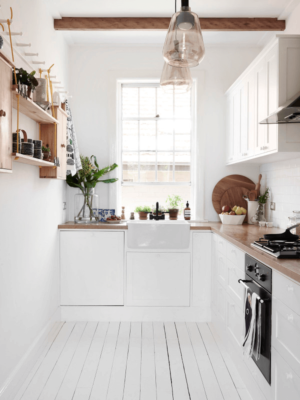By leaving one wall open and clutter free, this space feels as if it has room to spare, even though square footage is tight. Clever storage solutions hung at the highest part of the wall also give this kitchen an open and organized feel.