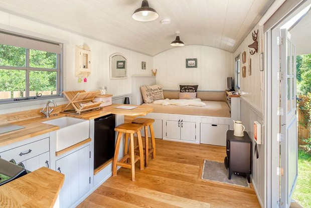 This petite pad in Australia is the epitome of tiny home coziness. While everything seems to be fitted into a space the size of an RV, things couldn't feel more inviting and spacious. With a large window over the kitchen sink and plenty of counter space, this kitchen has everything you need, and then some.  (Wait, is that a wood burning stove?)