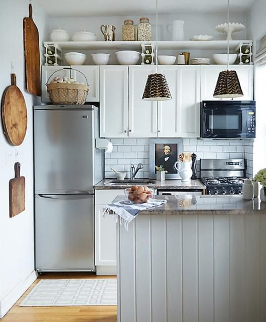 Not every micro kitchen needs a modern design in order to work.  Instead of incorporating the appliances into the cabinetry, this space is happy to keep everything on display. The resulting feel is eclectic, rustic, and almost old-world with cutting boards, dishes, and a vintage portrait on display.