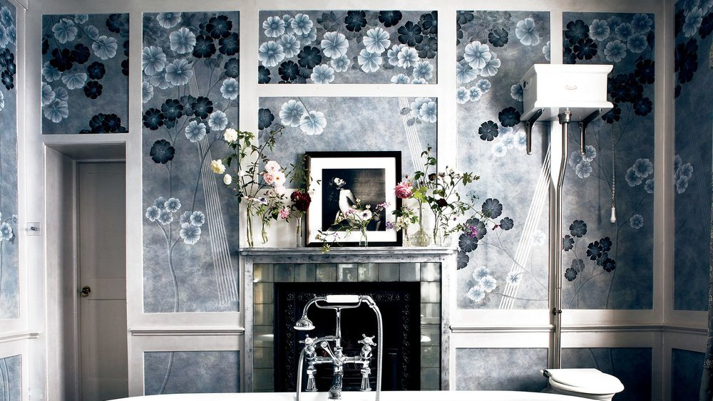 De Gournay's hand-painted Anemones on custom Xuan paper in dusk covers her master bath, where an Irving Penn portrait of the model sits above a mirrored-and-stone hearth, behind a claw-foot tub by Drummonds.