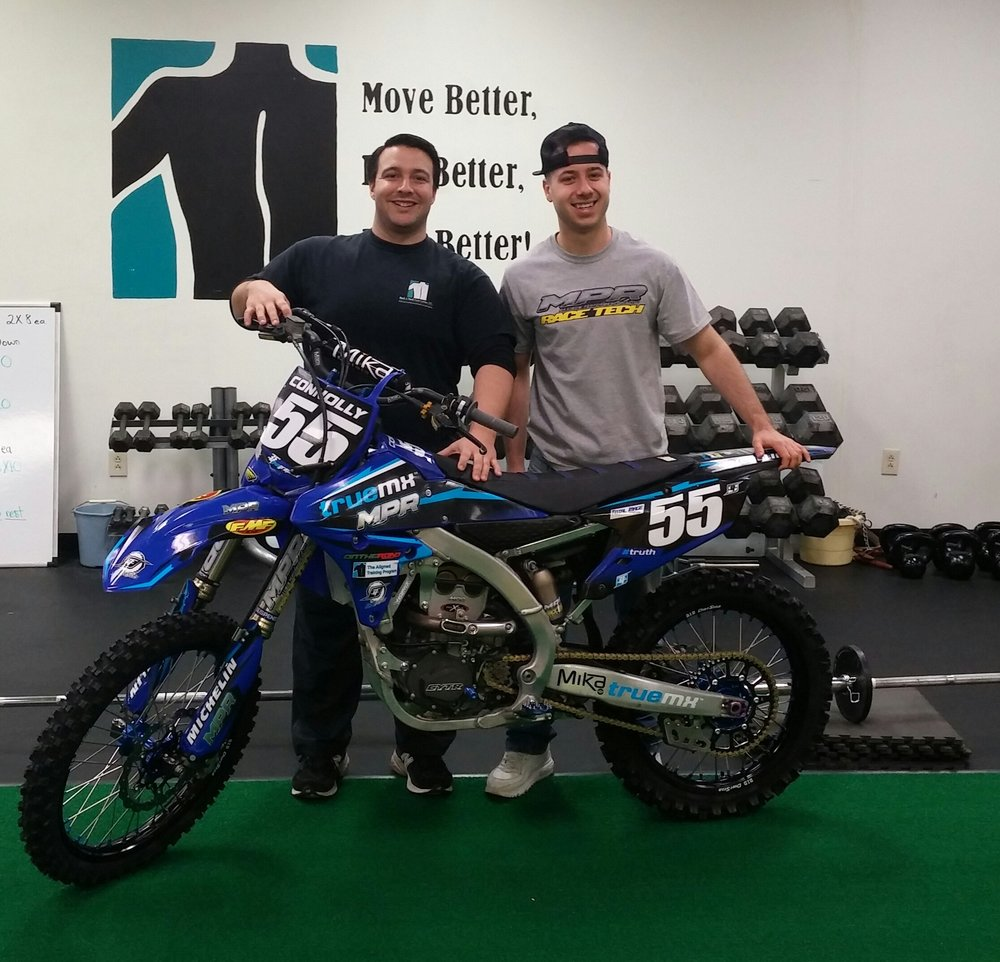 Ryan and Coach Bobby, in the Aligned gym, showing off his newest bike.