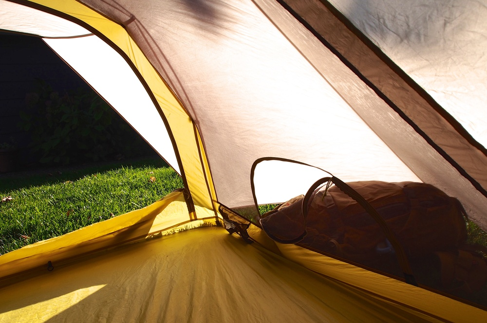 Vestibules are removed to the side of the tent meaning no more crawling over gear when entering or exiting the tent.  Access to the vestibules is easily accomplished by two half-circle zippers on either side of the tent as picture above.