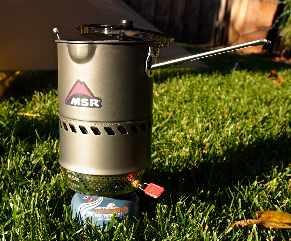 The design of the MSR Reactor stove burner as pictured here provides a stable platform for boiling water.  The valve that controls the amount of fuel burned is durable and easy to use.  The wind screen of the burner (the part with the holes between the canister and the pot) is not completely wind proof but is very close to it.  Unless you're on a windblown ledge somewhere battling a hurricane, you'll be just fine.