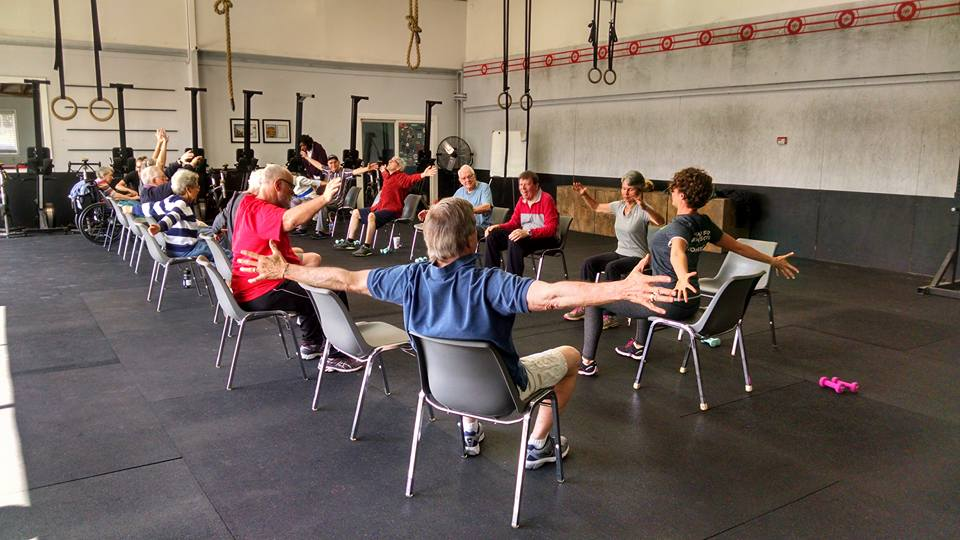 Sarah leading a Parkinson's group fitness class with seated PWR!Moves