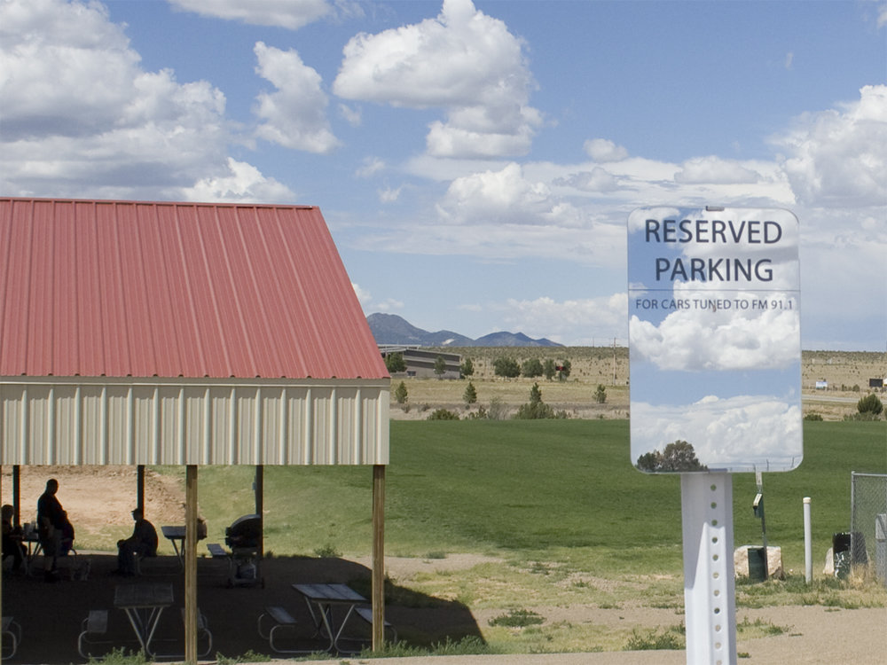 """Transmissions 2017, Socially engaged project and installation with four radio transmitters and mirrored acrylic signs, dimensions variable A four-channel sound installation for car radios, commissioned by the New Mexico Department of Cultural Affairs for the Edgewood, NM Town Park and Pavilion. The audio featured a conversation among three of the town's residents on the topic of """"persistence and change,"""" a theme chose by the New Mexico DCA. Each voice in the conversation was recorded separately and then broadcast on a separate radio transmitter. Thus, multiple cars and viewers will had to be present to hear the entire conversation. A fourth radio transmitter broadcast a field recording of wind blowing at the site, a prominent and persistent environmental feature in Edgewood"""