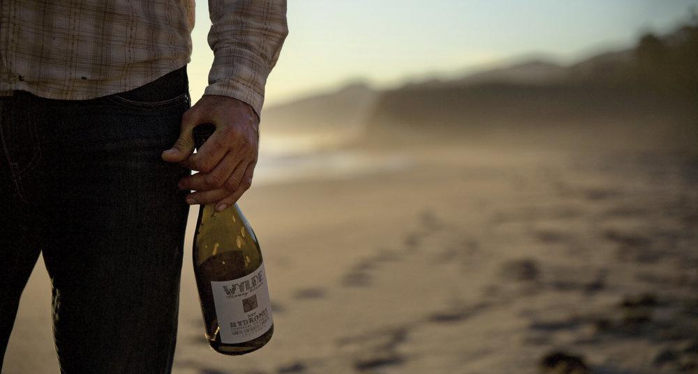bottle in hand at beach.jpeg