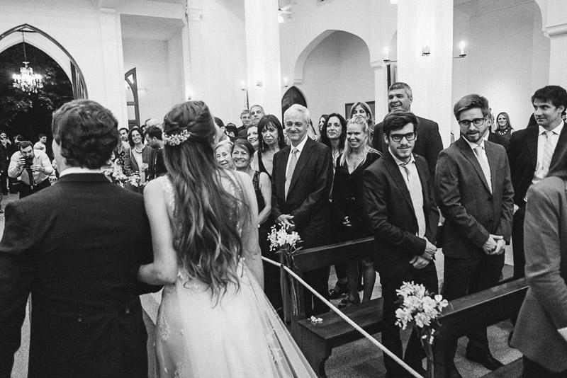 novios saliendo de la iglesia mientras saludan amigos