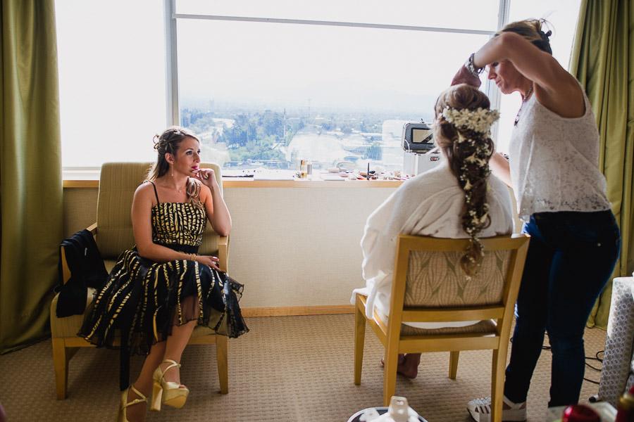 novia maquillandose, mientras su amiga la observa con gesto de felicidad