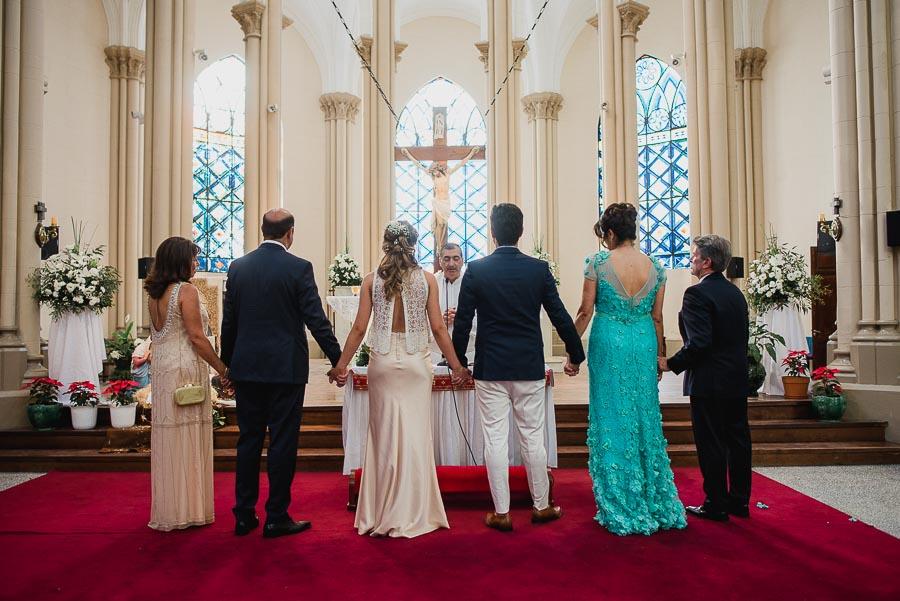 toda la familia tomada de la mano frente al altar