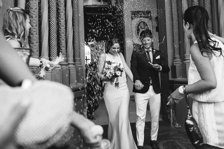 salida de los novios ya casados bajo una lluvia de arroz