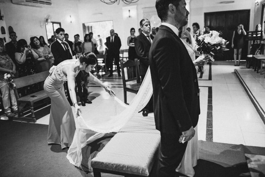 hermana de la novia acomoda el velo  de Emilia