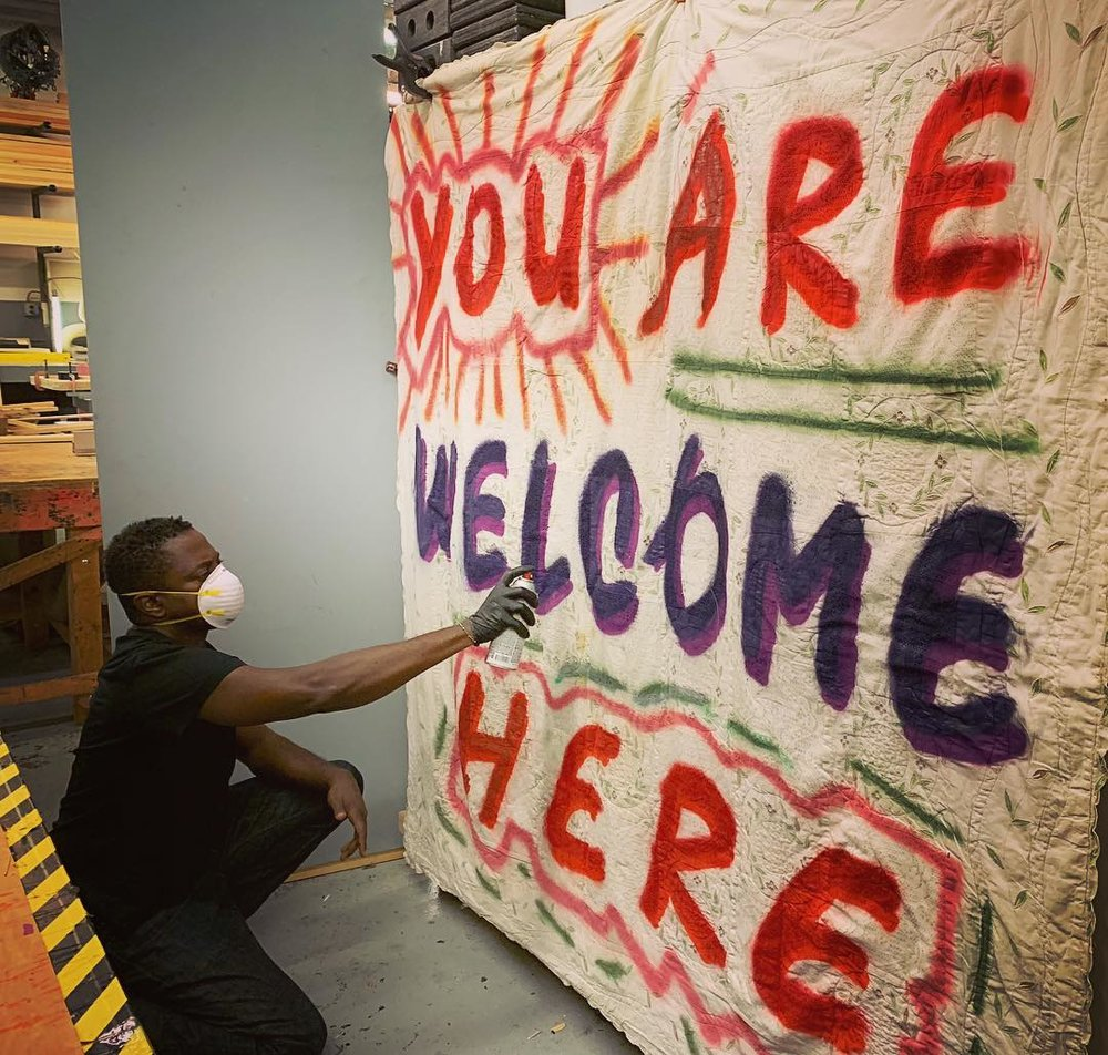 Set designer Sanford Biggers spray paints a quilt for the premiere at the BAM Harvey Theater