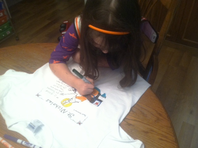 As you can see the iphone camera is not cutting it for a pretty picture, but you can see some progress, right?  This is Sweetie starting out with her shirt (a small), and yes, she is wearing a smock to prevent any accidental stains (these markers are made to STAY on the fabric).