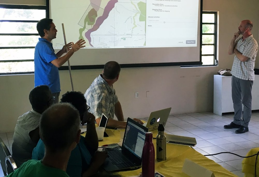 The Blue Halo Montserrat Steering Committee meets on April 10, 2017, to discuss ocean zoning options. Here, a stakeholder presents a zoning concept drafted in SeaSketch.
