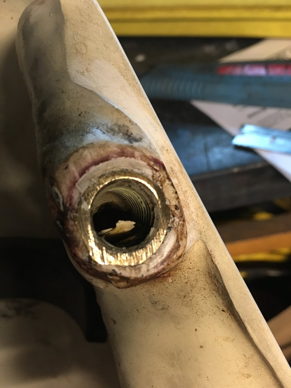 The bung on the opposite side was gouged even worse, concealed by a layer of paint. Clearly not just an oversight, but a consistent fail. There was a lot of red residue from gas that wicked up under the tank.