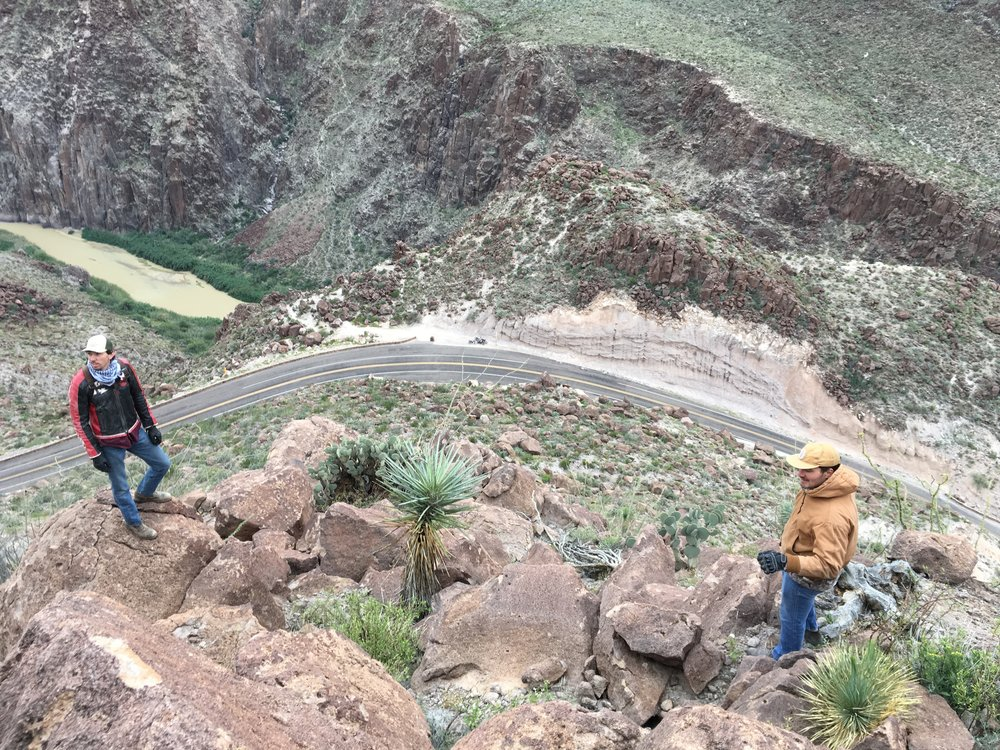 Jake's brother, Daniel and Paul Risse up the side of a mountain, and our bikes seen as small dots on the roadside below. The Rio Grande river can be seen on the left, with Mexico on the other side.