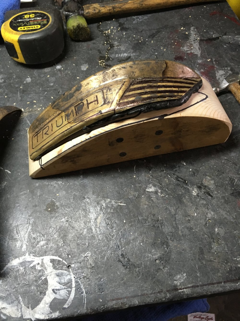 A buck was made of wood to fit the contour of the pieces. The back of the piece was filled with pitch and then laid on top.