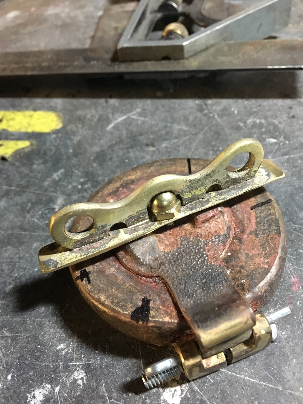 The lower half of the hinge was made from brass billet and soldered to a ring that clamps tightly to the filler neck. There are blocks of brass soldered inside the ring to rest on the edges of the tank neck where the regular cap grips it. There will be a little more shaping of the locking lever, and the patina of the cap will be made a little more uniform.