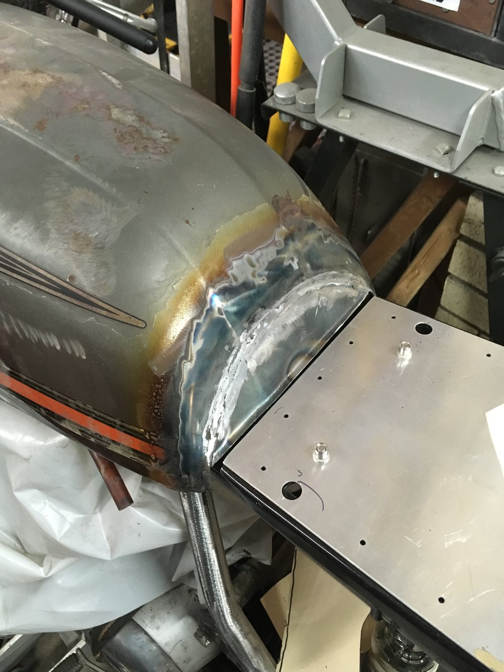 A thin steel cover was welded in extending the tank character lines as well. The tank edge was heated and bent downward in line with the new panel, and then welded only on the outermost edge of the tank's pinch welded seam, to keep from having to weld the tank skin directly.
