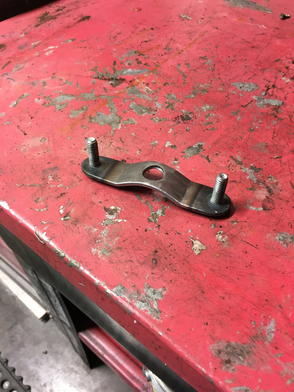 The rear tank hold-down bracket waiting to be welded on. I usually try to get all the brackets made while the bike is in the assembly area of the shop and then get them all welded on at once, reducing the time the bike is in the metal room potentially getting exposed to grinding dust.