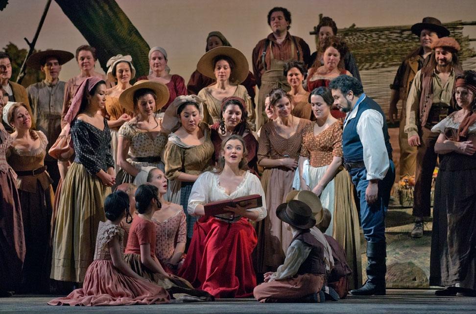 Adina (played by Andriana Chuchman) reading to the chorus in Donizetti's  L'Elisir d'Amore . Photo: Ken Howard/Metropolitan Opera