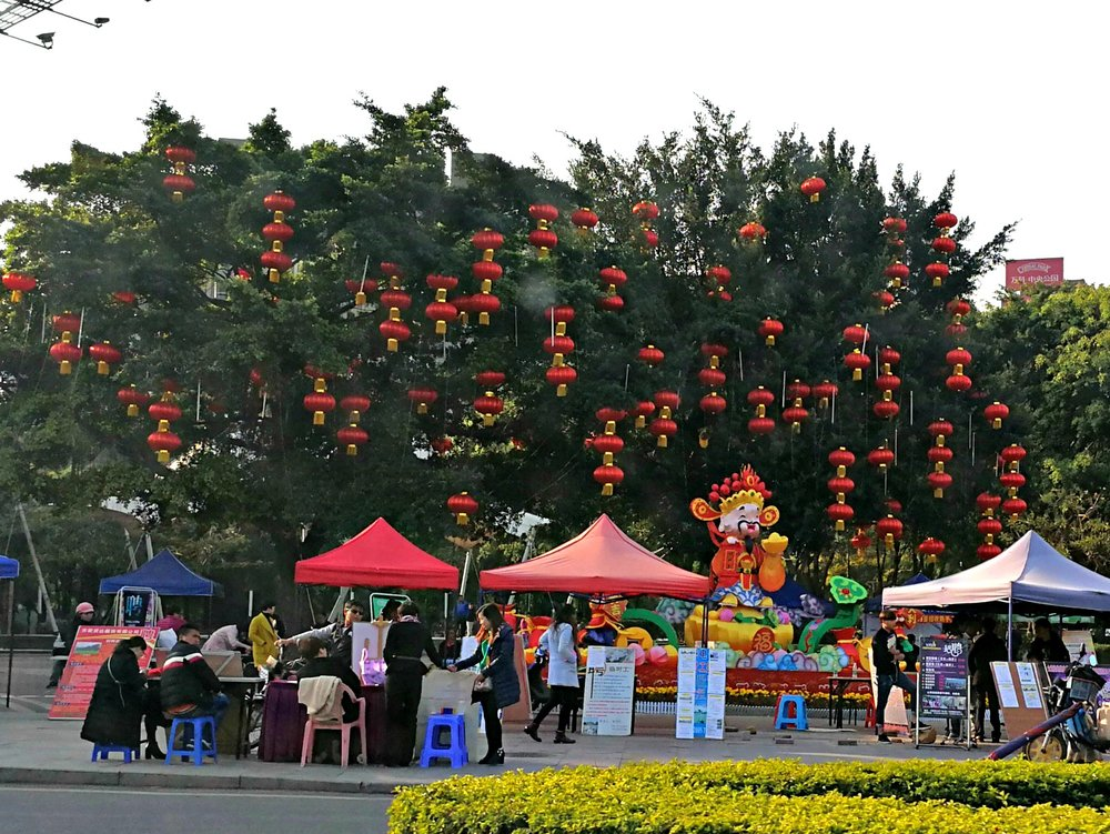 This picture shows both smaller red lanterns in the trees, and a large silk decorative lantern of the God of Wealth, which seems appropriate as this is the area where the job fair is held!