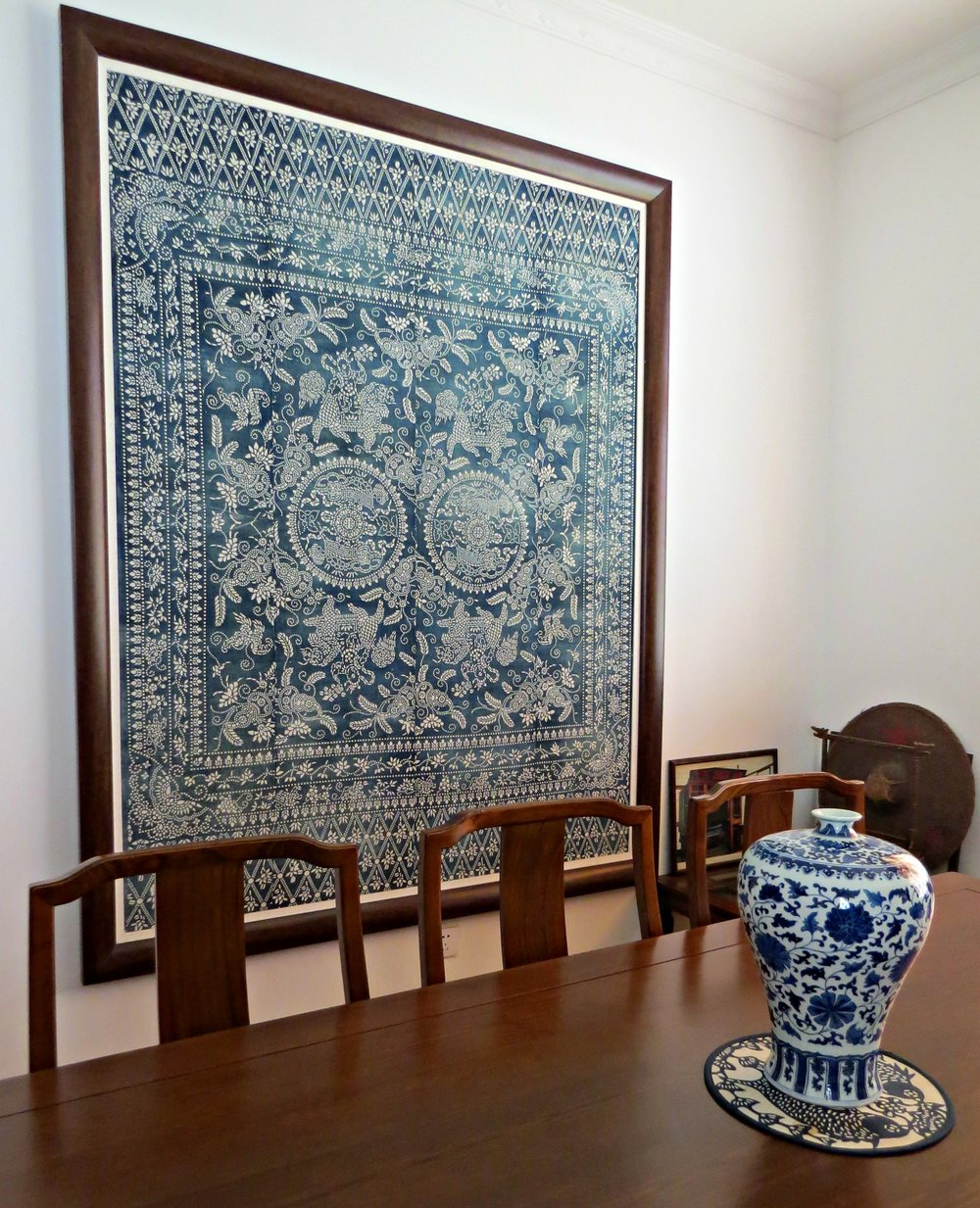 A framed piece of antique cloth, displayed with some blue and white pottery at the Chinese Blue Nankeen Exhibiton Hall in Shanghai