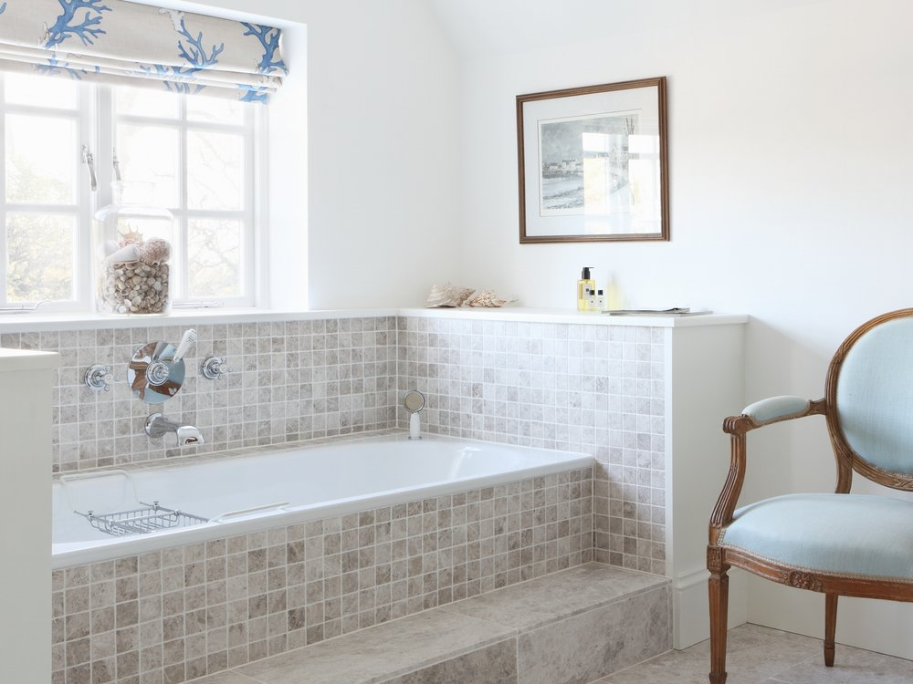This is from our Turnkey project. We love the pale blue armchair and the seashells surrounding the bath.  Click here to see the entire project.