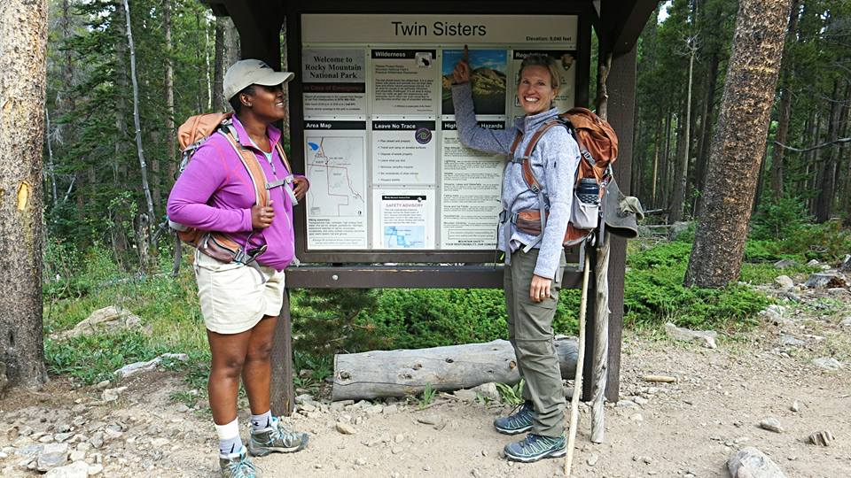 """I am pointing at a sign with Lenora that says """"Twin Sisters"""""""