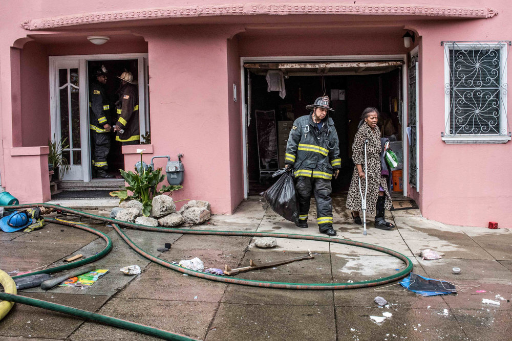 A San Francisco firefighter assists a woman outside of her home after her neighbor's house on Plymouth Avenue sustained major fire damage on Monday, June 29, 2015 in San Francisco.  (Michael Ares/Special to the S.F. Examiner)